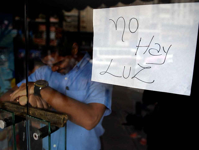 """An employee of a business closed during a blackout stands behind the door with a notice reading """"There's No Light"""", in Caracas on September 3, 2013. Major power blackouts paralyzed Venezuela's capital and several states across the country on Tuesday but there was no official explanation for the cause. AFP PHOTO/Juan Barreto (Photo credit should read JUAN BARRETO/AFP/Getty Images)"""